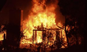 Fire engulfs a house as firefighters battle the Powerhouse wildfire at the Angeles National Forest in California